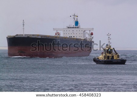 Cargo ship and tug boat in the ocean