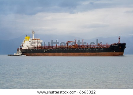 cargo ship and tugboat at the sea