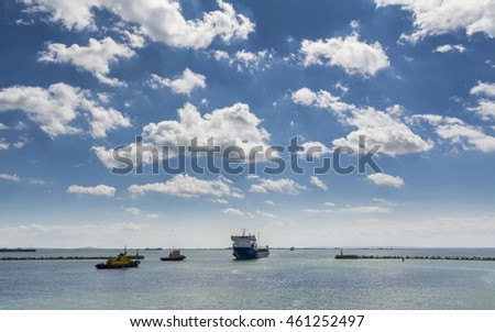 Cargo Ship and Tugboat. Seascape with beautiful sky.