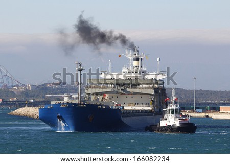 Cargo ship arriving at port, assisted by tugboat - stock photo