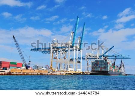 Cargo ship at Miami harbor with crane and blue sky over sea. - stock photo