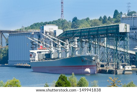 Cargo ship at the industrial building loading, unloading  in the harbor, port, terminal. Vancouver, Canada. - stock photo