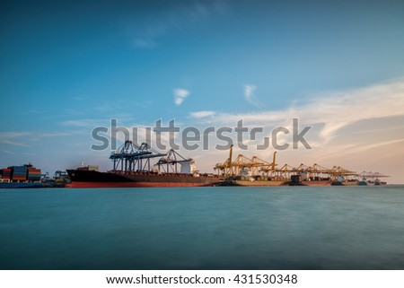 Cargo ship at Trade Port harbor with crane and blue sky over sea at sunrise