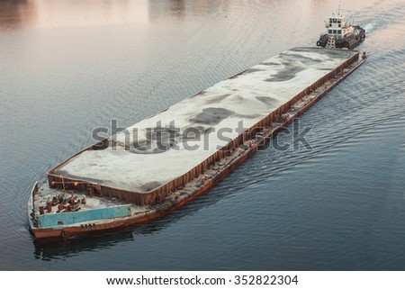 Cargo ship barge loaded with sand. Sunset. - stock photo