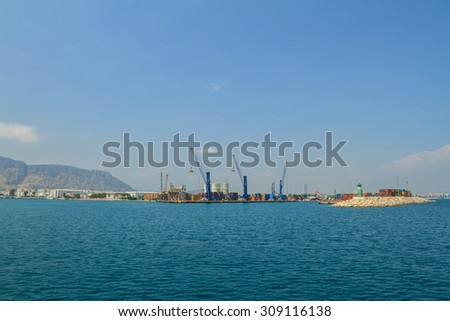 Cargo ship, containers and cranes in sea port. Container ship in Turkish sea port. logistic center. big cargo ship at big sea port with lots of cranes, blue cloudy sky in background
