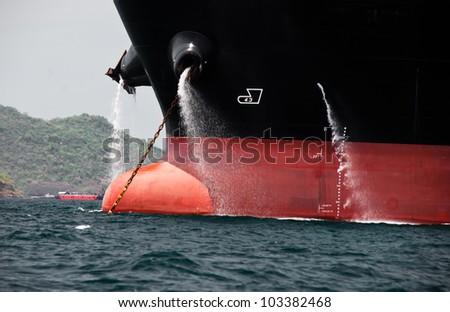 Cargo ship drain water to the Ocean - stock photo