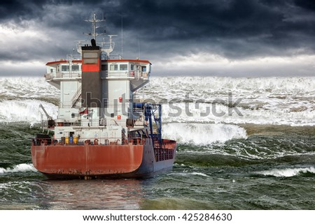 Cargo ship during storm in ocean. - stock photo