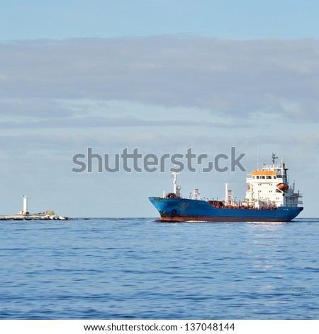 Cargo ship entering port with lighthouse at the background