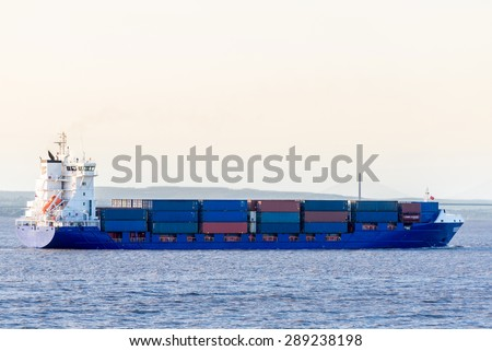 Cargo ship in sunset lights, at Bristol channel.The Second Severn Crossing bridge in background.  - stock photo