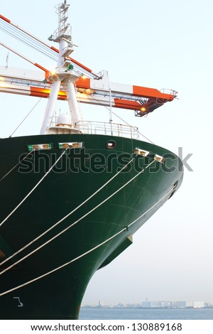 Cargo ship in the harbor at sunset - stock photo