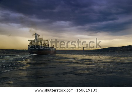 Cargo ship in the harbor at sunset.