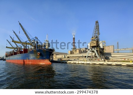 Cargo ship in the harbor at sunset. Gdansk, Poland. chemical wharf, loading vessel - stock photo