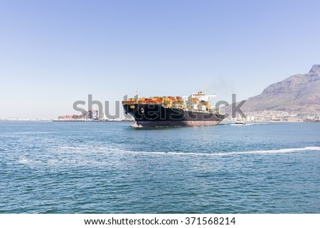 Cargo ship loaded with containers sailing away, land and harbour can be seen in the background.