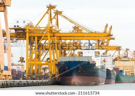 Cargo ship loading containers at harbor terminal - stock photo