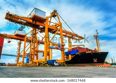 Cargo ship loading containers at work - stock photo