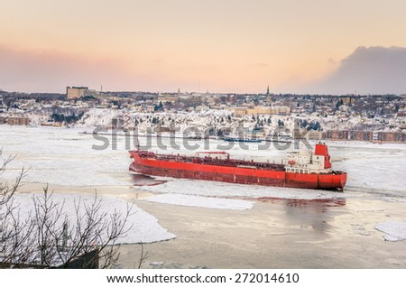 Cargo Ship on a Frozen Saint Lawrence River at Sunset - stock photo