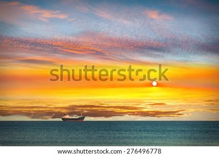 Cargo ship on calm sea in the morning. - stock photo