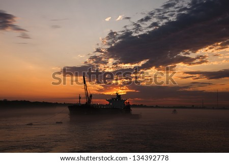 Cargo ship on Mississippi river at sunset - stock photo