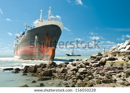 Cargo ship run aground on rocky shore waiting for rescue  - stock photo