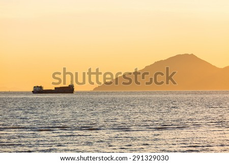 Cargo ship sailing at sunset - stock photo