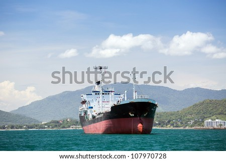 cargo ship sailing in front of the mountain - stock photo