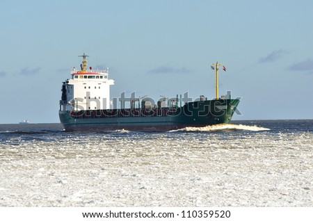 cargo ship sailing in sea full of ice in winter