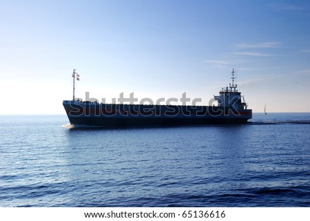 cargo ship sailing in still water heading for the port. Silhouette - stock photo