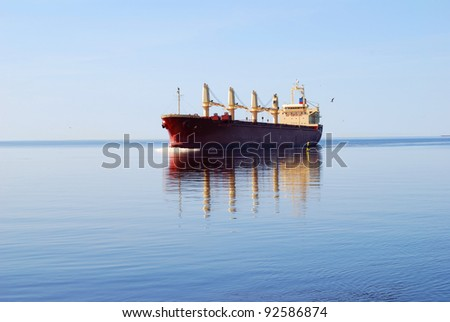 cargo ship sailing in still water near port of Riga