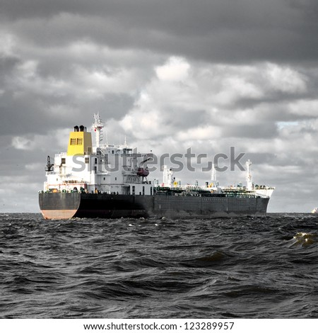 cargo ship sailing in stormy weather near port of Riga