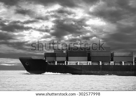 Cargo ship travel on the ocean with cloudy sky background - stock photo