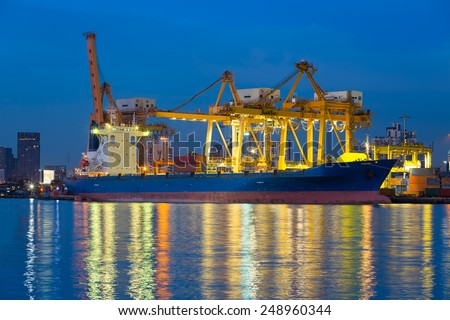 Cargo ship unloading container at port,  twilight time. - stock photo