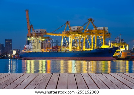 Cargo ship working with crane at port reflect on river, twilight time. - stock photo
