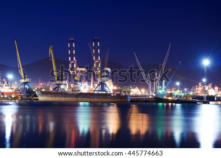 Cargo ships in the container terminal. Illuminated cargo port at night with container terminals.