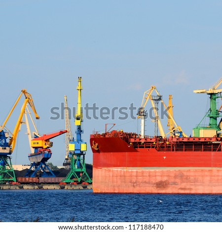 Cargo terminal of Riga, Latvia. Cranes loading ship with coal - stock photo