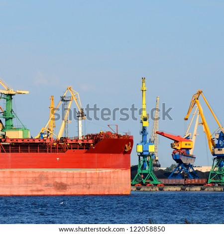 Cargo terminal of Riga, Latvia. Cranes loading ship with coal - stock photo