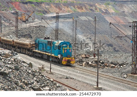 Cargo train carrying iron ore on the opencast mining quarry - stock photo