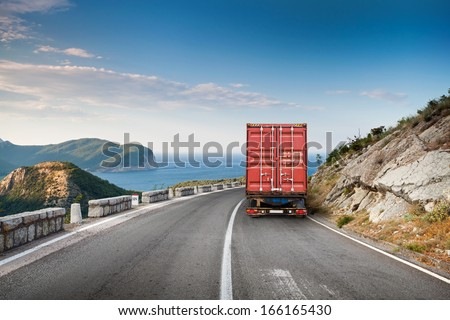 Cargo truck on the mountain highway with blue sky and sea on a background - stock photo