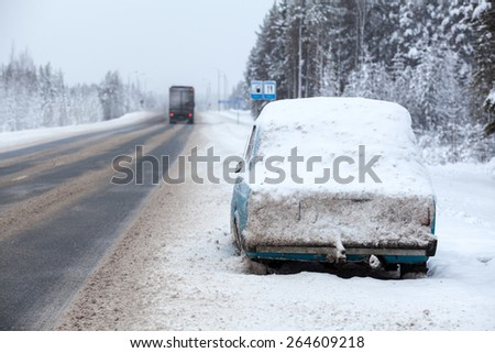 Cargo trucks driving along broken and abandoned on roadside car in snow and ice. Winter highway in north of Russia - stock photo
