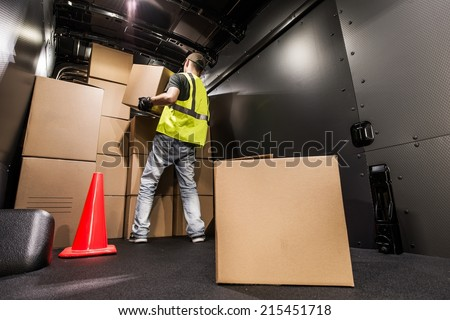 Cargo Van Loading by Worker. Man Carrying Boxes In the Cargo Van For Customer Delivery. Shipment Preparation and Processing. - stock photo