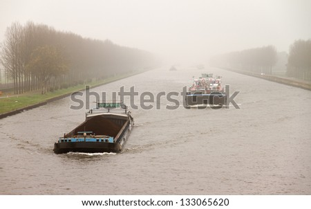 Cargo vessels sailing on a foggy Amsterdam-Rhine Canal in the Netherlands