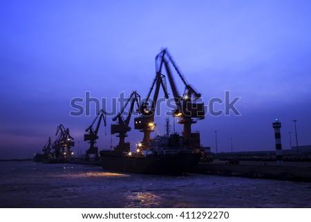 Cargo wharf crane at night - stock photo