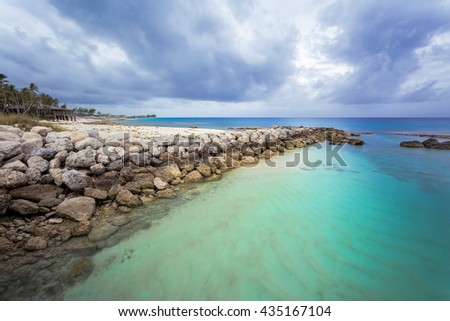 Caribbean beach with white sand coastline and deep blue sea, Nassau, Bahamas. Amazing lonely beach with a typical tropical cloudy day. - stock photo