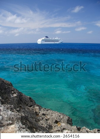 Caribbean blue water with a cruise ship in the background - stock photo