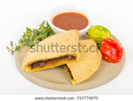 Caribbean Jerk Beef Patty - Jamaican spicy minced jerk beef with onions and peppers in short crust pastry and scotch bonnet chillies on a white background. - stock photo