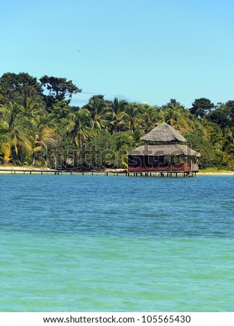 Caribbean restaurant on stilts with thatch roof over the sea and a tropical beach with lush vegetation in background - stock photo