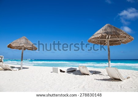Caribbean sea coastline with grass sun umbrellas and wooden beach beds. Vacation concept  - stock photo