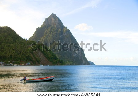 Caribbean Sea native fishing boat  with view twin piton peaks and volcano mountains  Soufriere St. Lucia island West Indies - stock photo