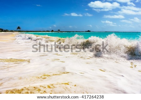 Caribbean sea wave near white sand beach at sunny summer day paradise in Cuba. Sea waves at paradise sea beach. Island beach with blue sea water. Sea foam from big wave on a beach. Sea wave foam. - stock photo