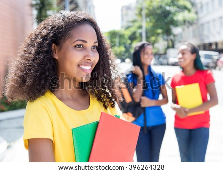Caribbean student looking sideways in the city with friends - stock photo