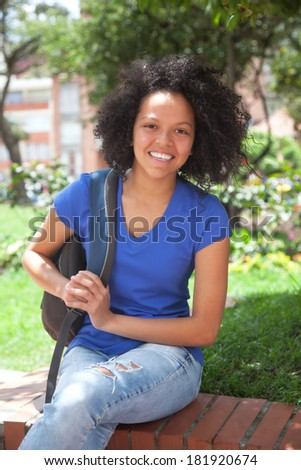 Caribbean student sitting in a park - stock photo